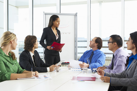 business woman standing: Businesswoman Conducting Meeting In Boardroom