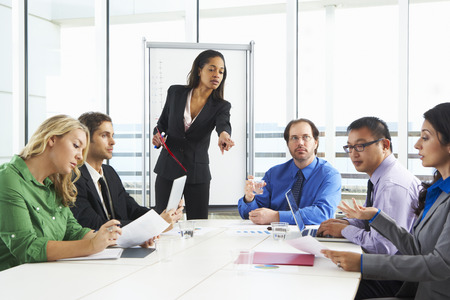 conducting: Businesswoman Conducting Meeting In Boardroom