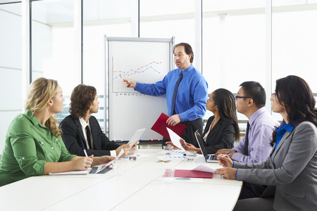 conducting: Businessman Conducting Meeting In Boardroom