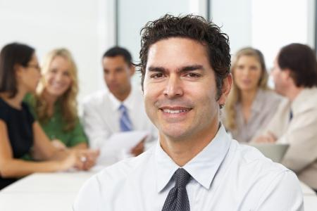 Boardroom meeting: Portrait Of Businessman Sitting At Boardroom Table