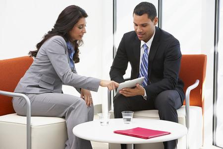 women talking: Businessman And Businesswoman Having Informal Office Meeting