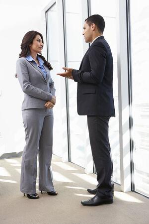 dos personas hablando: Empresarios que tienen reunión informal en la Oficina