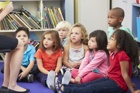 asian teacher: Elementary Pupils In Classroom Working With Teacher