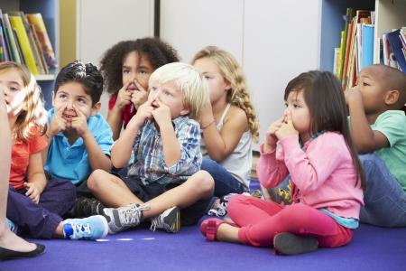 escuelas: Grupo de alumnos de primaria en sala de clase tocar las narices