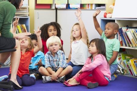 Groep van basisschoolleerlingen in de klas beantwoorden vraag