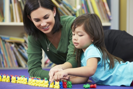 numeracy: Elementary Pupil Counting With Teacher In Classroom Stock Photo