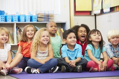 les geven: Groep van basisschoolleerlingen in de klas Stockfoto