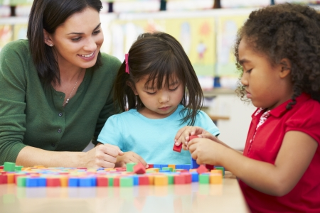 child learning: Elementary Pupils Counting With Teacher In Classroom