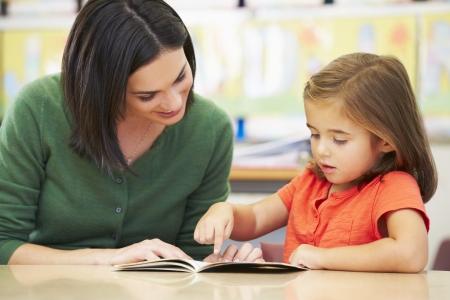 niños leyendo: Alumno Primaria Lectura con el profesor en el aula