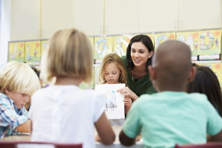 teaching crayons: Elementary Pupil Showing Drawing To Classmates In Classroom Stock Photo