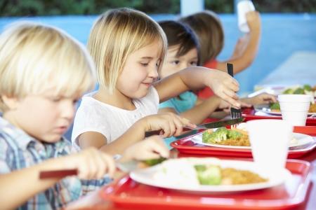 Los alumnos de primaria de disfrutar del almuerzo saludable en la cafetería