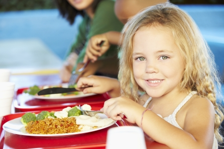 cafeteria tray: Elementary Pupils Enjoying Healthy Lunch In Cafeteria
