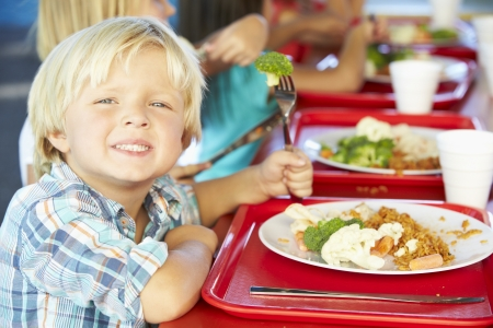 school cafeteria: Elementary Pupils Enjoying Healthy Lunch In Cafeteria
