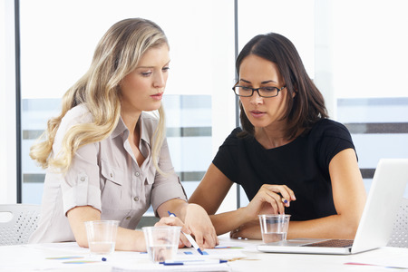 discussing: Two Businesswomen Meeting In Office Stock Photo
