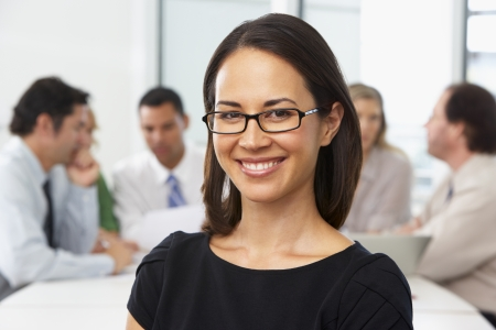 Portrait Of Businesswoman Sitting At Boardroom Table photo