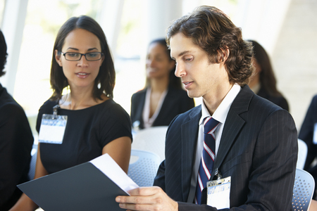 delegates: Businessman Discussing Conference Document With Colleague Stock Photo