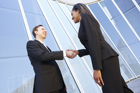 business handshake: Businessman And Businesswomen Shaking Hands Outside Office