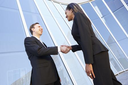 cerrando negocio: El hombre de negocios y empresarias que sacuden las manos fuera de la oficina