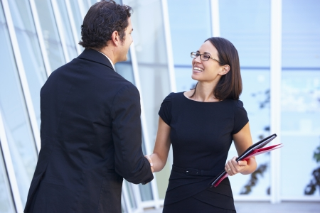 two hands: Businessman And Businesswomen Shaking Hands Outside Office