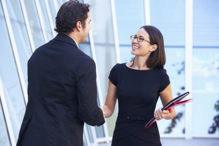 dos personas platicando: El hombre de negocios y empresarias que sacuden las manos fuera de la oficina