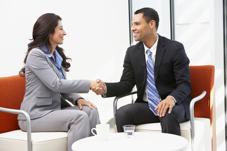 talking businessman: Businessman And Businesswoman Shaking Hands After Meeting Stock Photo