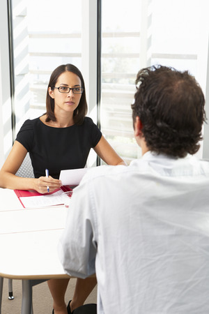 mixed race people: Businesswoman Interviewing Male Candidate For Job Stock Photo