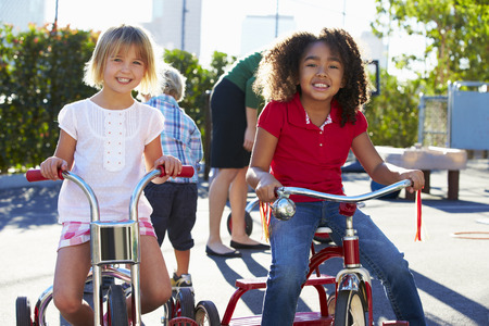 Zwei Mädchen Reiten Dreiräder im Spielplatz