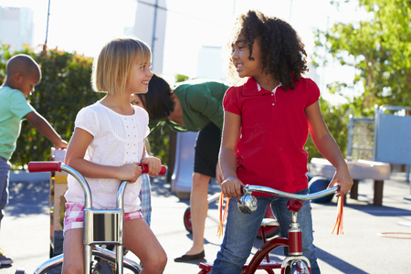 old school bike: Two Girls Riding Tricycles In Playground
