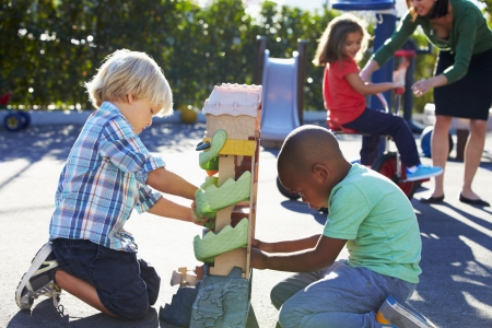 children playing together: Two Boys Playing With Toy In Playground