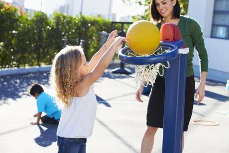 playground basketball: Teacher Supervising Breaktime At Elementary School