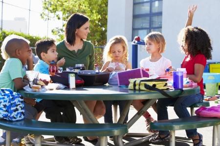 children playground: Los alumnos de primaria y maestra de comer el almuerzo Foto de archivo