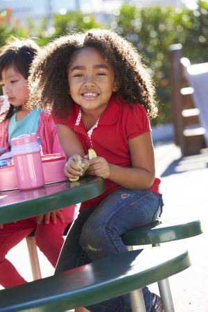 5 year old girl: Elementary Pupil Sitting At Table Eating Lunch Stock Photo