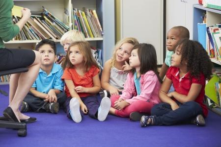 Groep van basisschoolleerlingen in de klas werken met Leraar