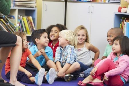salon de clases: Grupo de alumnos de primaria en el aula que escucha el profesor Foto de archivo