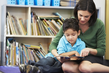 children reading: Elementary Pupil Reading With Teacher In Classroom