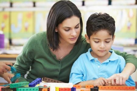 Elementaire Leerling tellen met leraar in de klas Stockfoto