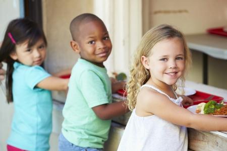ni�os comiendo: Los alumnos de primaria que recoge el almuerzo saludable en la cafeter�a Foto de archivo
