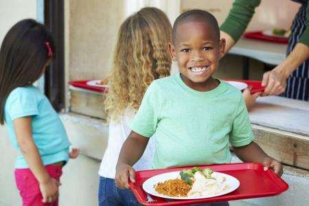 bandejas: Los alumnos de primaria que recoge el almuerzo saludable en la cafeter�a Foto de archivo