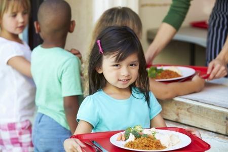 podnos: Základní Žáci Sbírání zdravý oběd v jídelně Reklamní fotografie