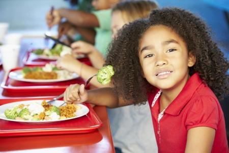 dieta sana: Los alumnos de primaria de disfrutar del almuerzo saludable en la cafeter�a Foto de archivo