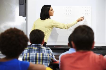 インタラクティブ ホワイト ボードを使用してクラスで立っている教師