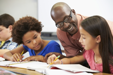 先生が生徒を教室の机で勉強して
