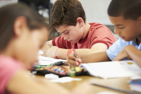 children reading: Pupils Studying At Desks In Classroom Stock Photo