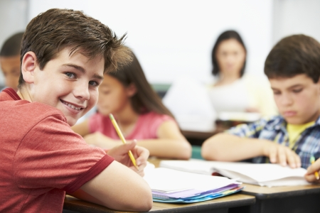 teaching children: Pupils Studying At Desks In Classroom Stock Photo