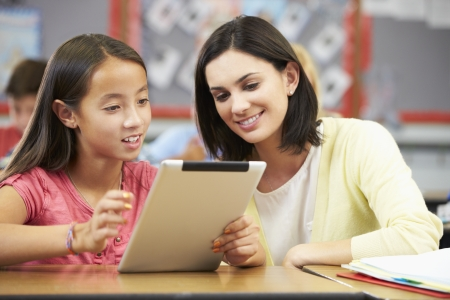 asian teacher: Pupils In Class Using Digital Tablet With Teacher