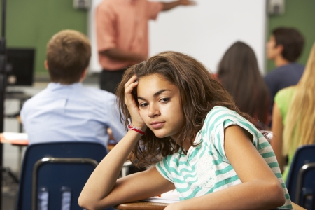 Bored Female Teenage Pupil In Classroom photo