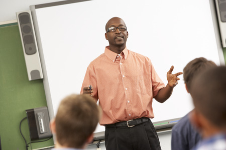 13 year old boy: Teacher Talking To Class Standing In Front Of Whiteboard