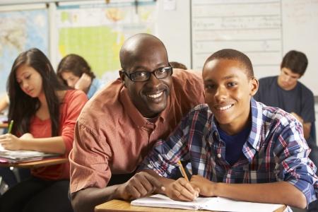 maestra ense�ando: Estudiantes de ayuda del alumno masculino de la universidad en el escritorio en el aula