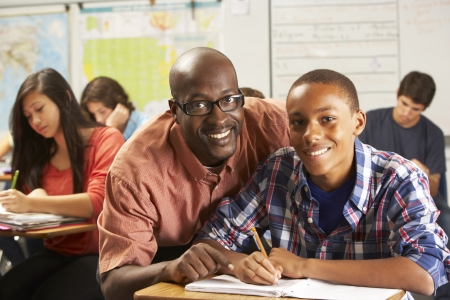 helping: Teacher Helping Male Pupil Studying At Desk In Classroom Stock Photo
