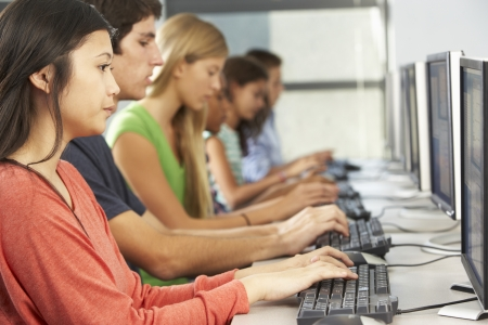 Group Of Students Working At Computers In Classroom photo